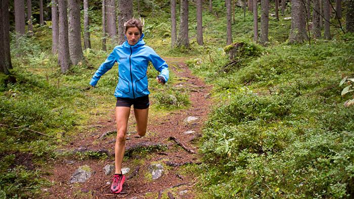 HOKA athlete Amandine Ferrato runs downhill through the forest