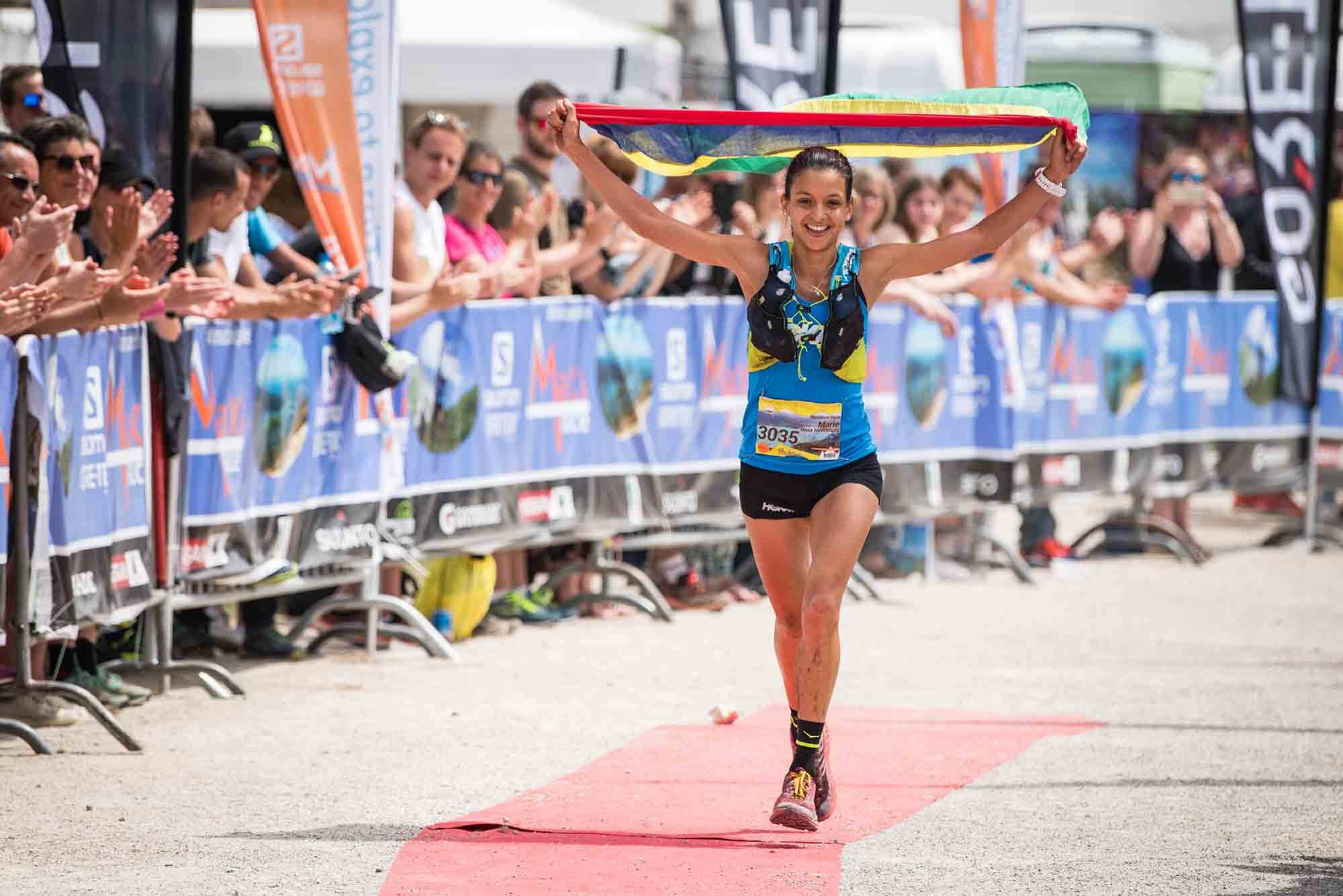 HOKA athlete Marie Perrier crosses the line with the flag of Mauritius