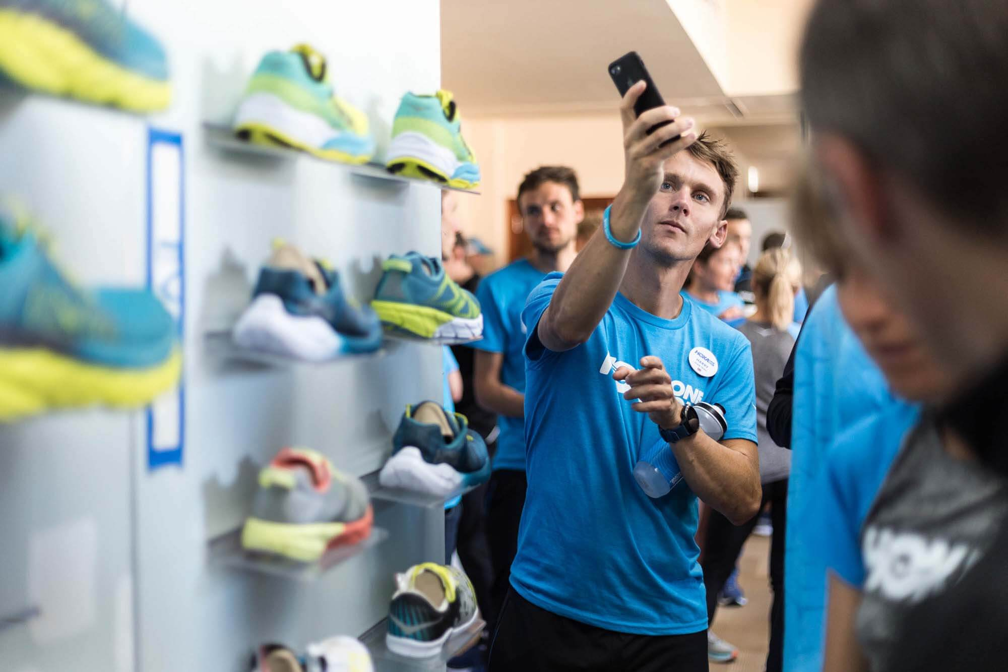 HOKA athlete Harry Jones takes a picture of HOKA shoes
