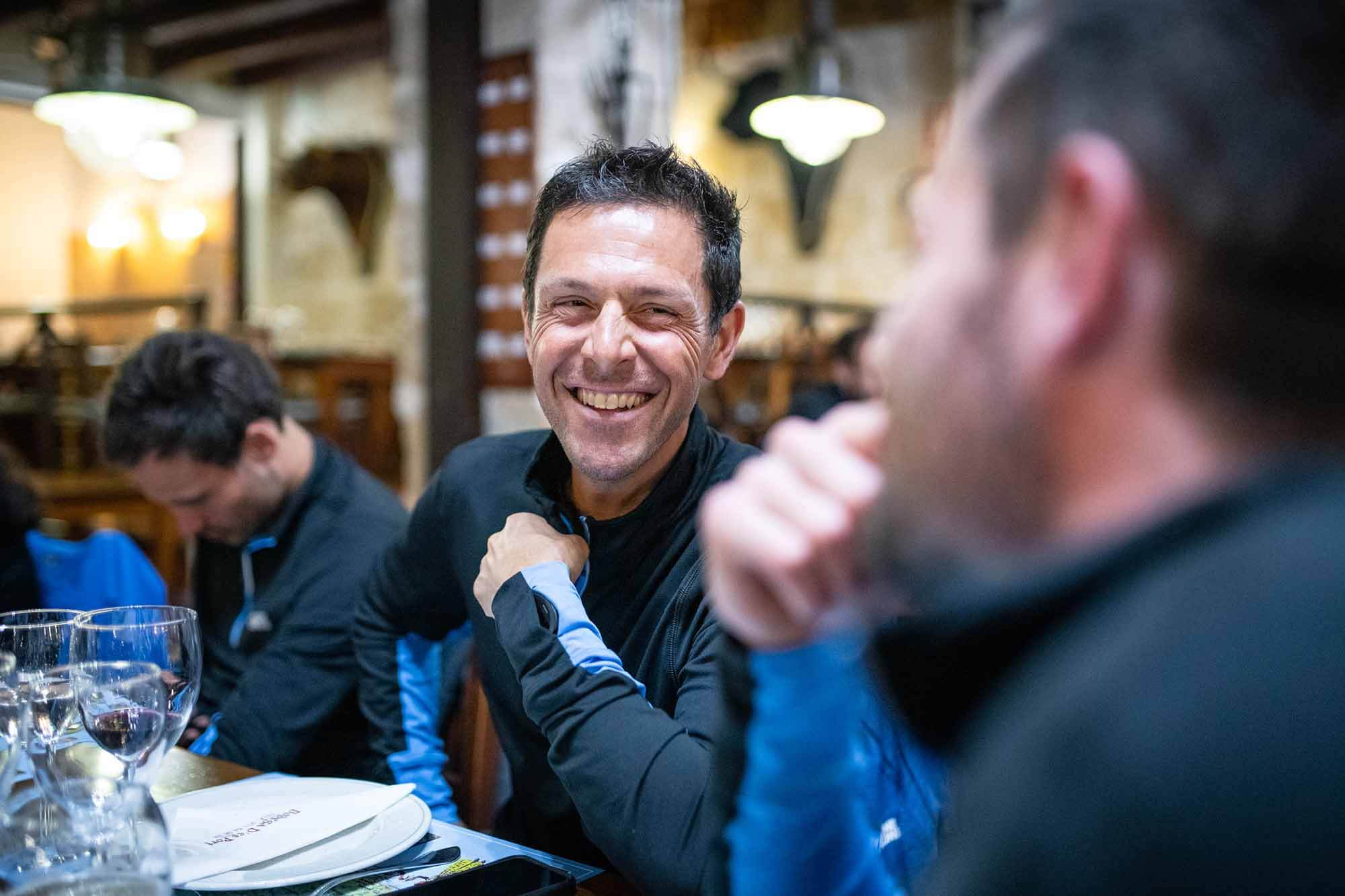 HOKA athlete and team manager Julien Chorier smiling at dinner