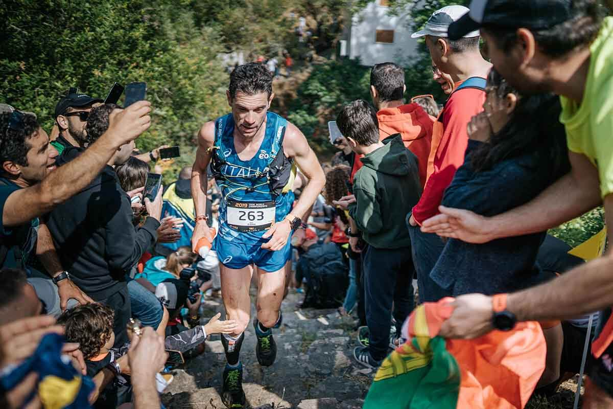 HOKA athlete Marco de Gasperi runs up a steep hill surrounded by supporters.