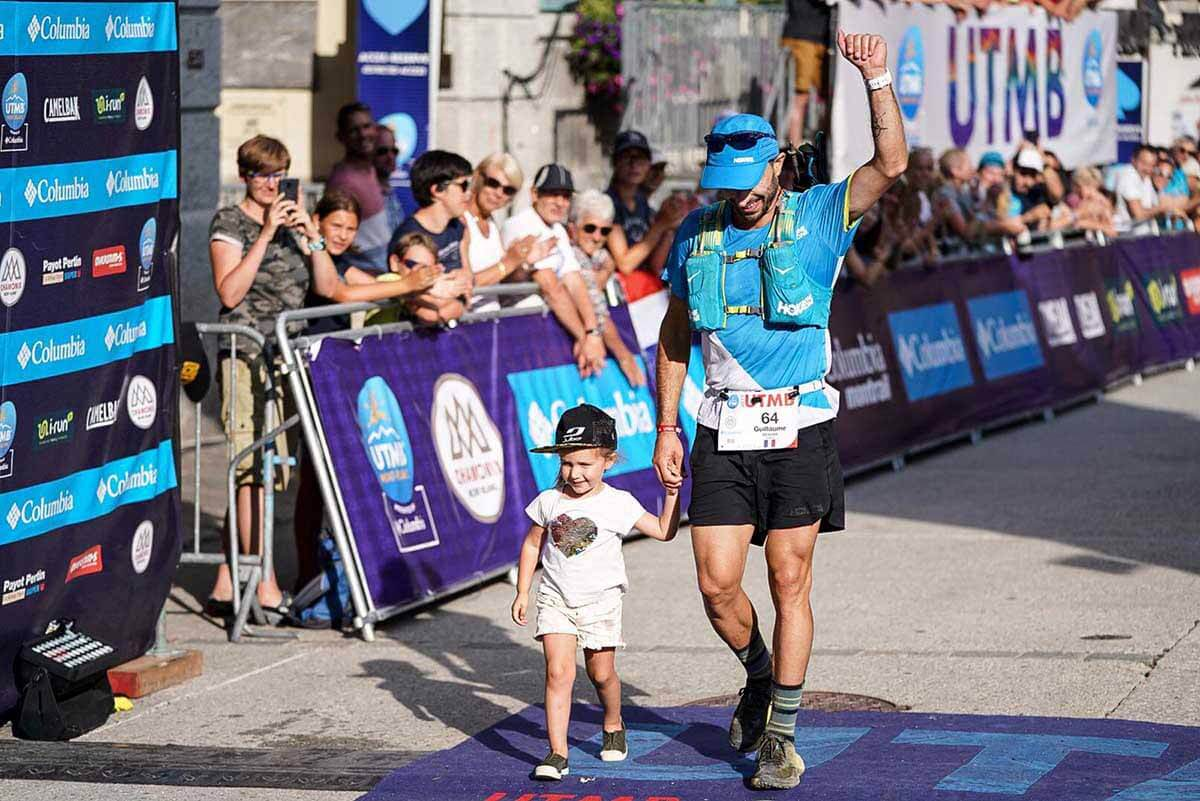 HOKA athlete Guillaume Beauxis with his child as he crosses the finish line