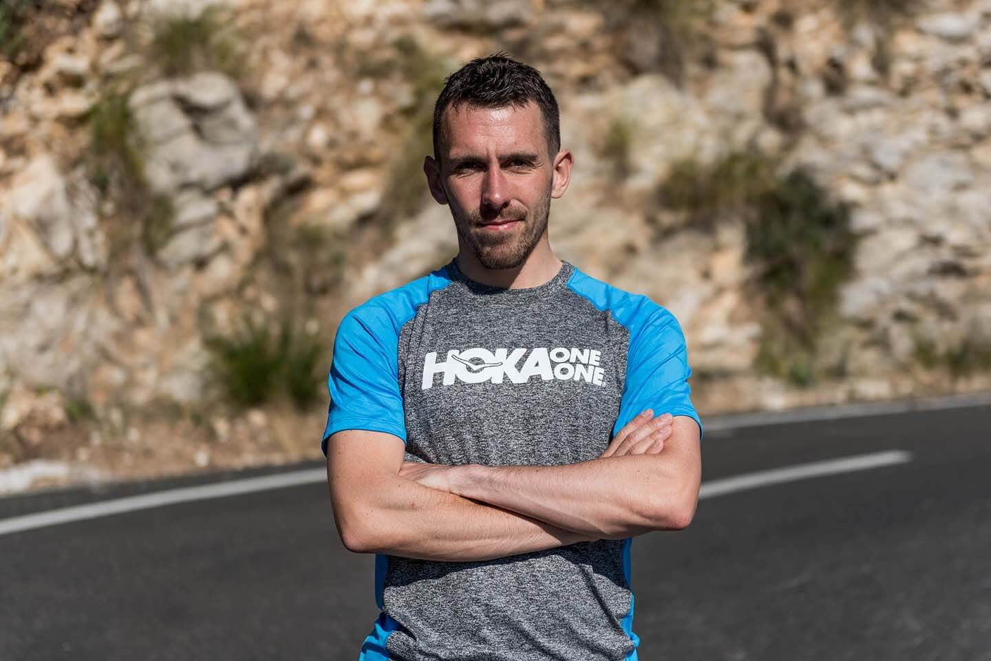 HOKA athlete Andrew Douglas stands with arms folded
