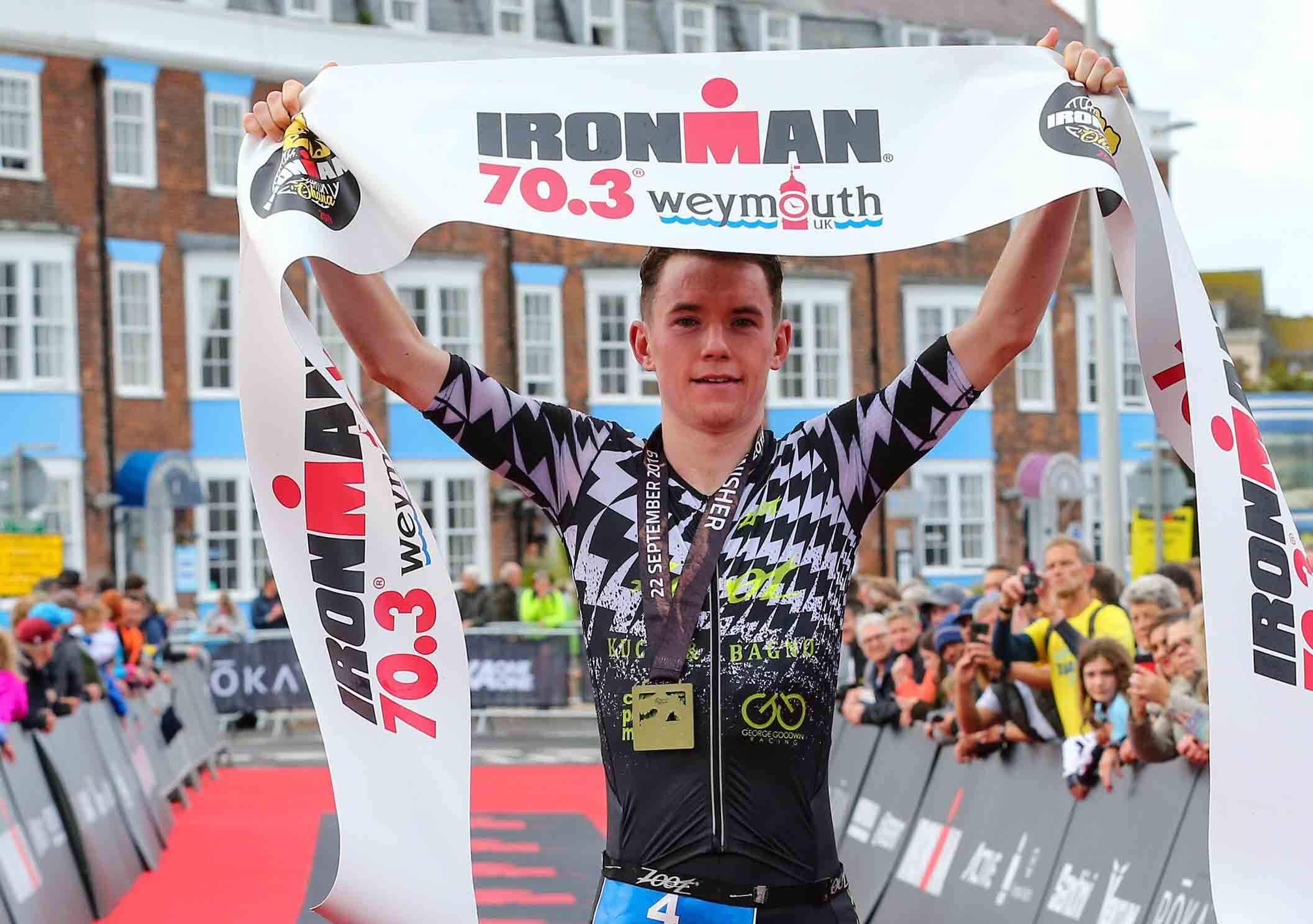 HOKA athlete George Goodwin holds up the finish tape