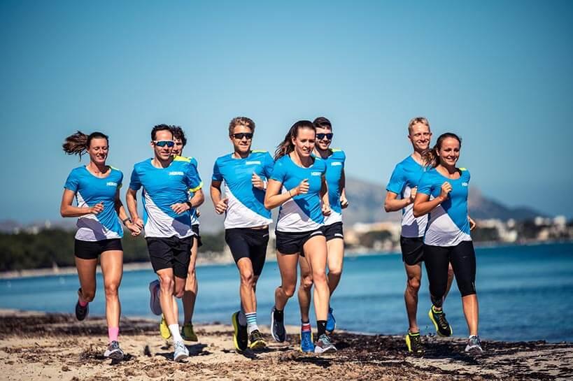 HOKA athletes run across the beach